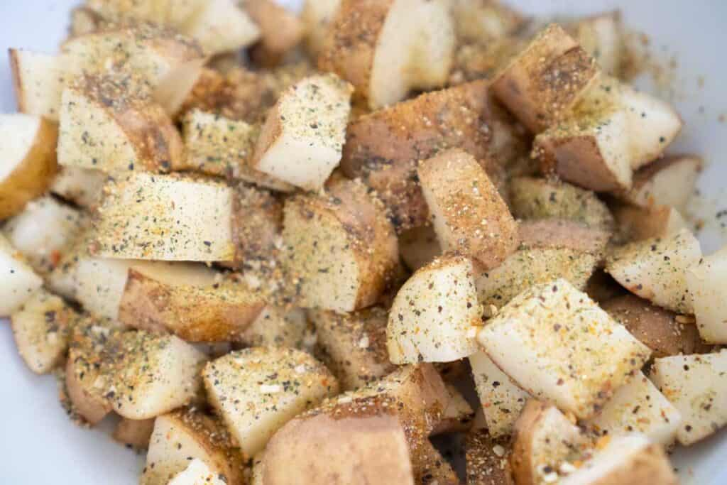 close photo of raw potato cut into 1 inch pieces covered in herb mixture