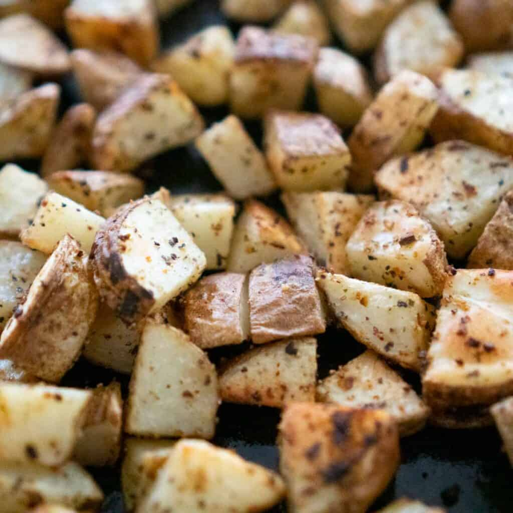close up of diced russet potatoes with herbs after roasting