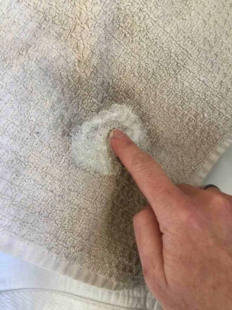 rubbing homemade stain remover in white towel with finger