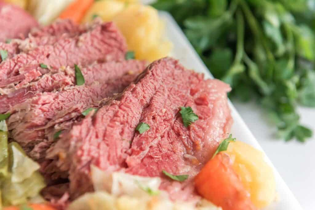 corned beef with cabbage and carrots and potatoes on white platter