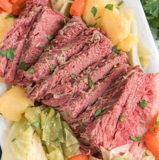 corned beef and cabbage on white platter with carrots and potatoes