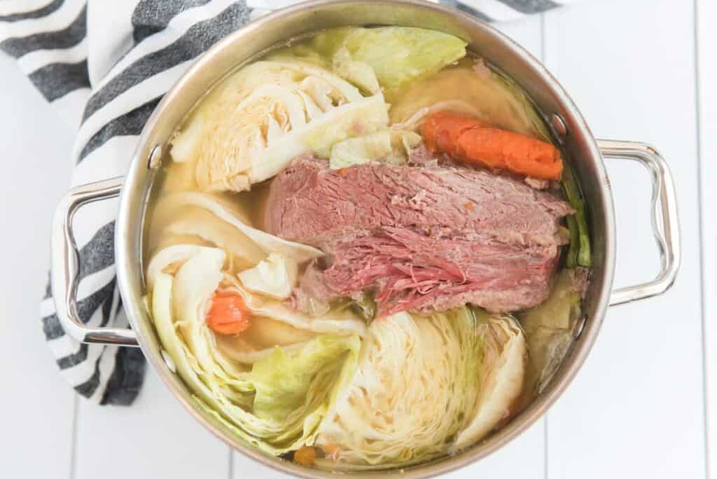 corned beef and cabbage with potatoes and carrots in stock pot