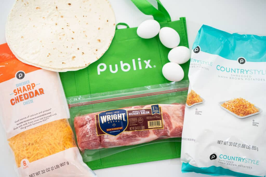 publix shopping bag with shredded cheese, eggs, tortillas, frozen hash browns and wright bacon