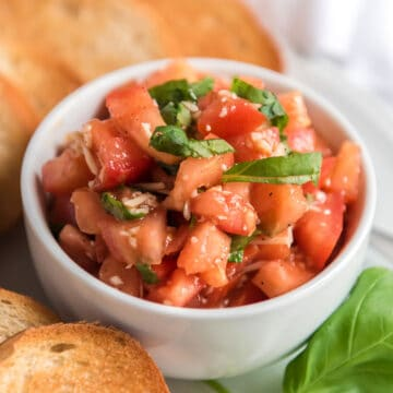 fresh bruschetta in white bowl with slices of french bread