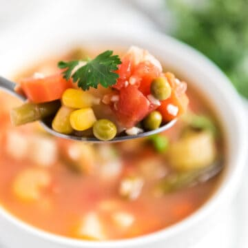 homemade vegetable soup in spoon over white bowl