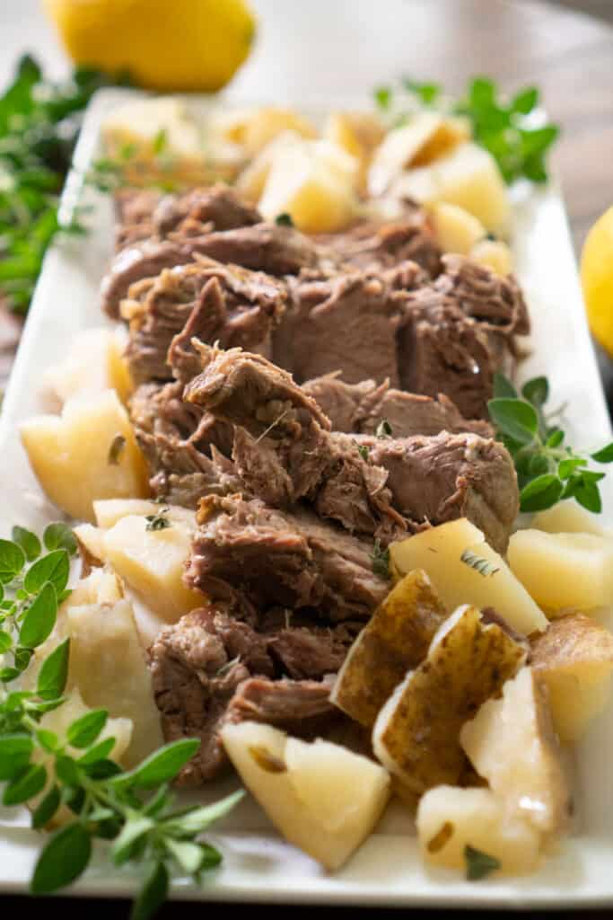 leg of lamb on white platter with potatoes garnished with oregano