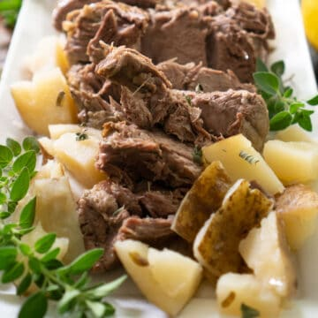 leg of lamb on white platter with potatoes garnished with oregano