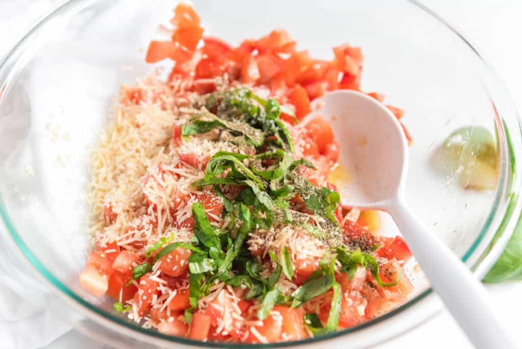 mixing bruschetta ingredients in a glass bowl with white spoon