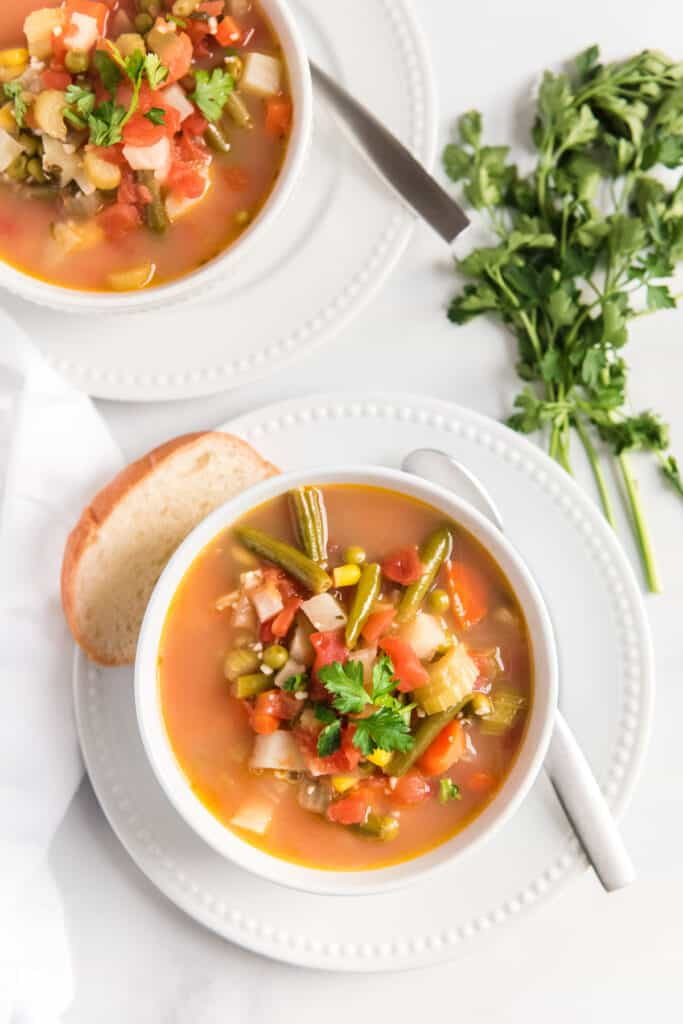 vegetable soup in two white bowls on a white plates with slice of bread and butter knife on white table with fresh parsley bunch