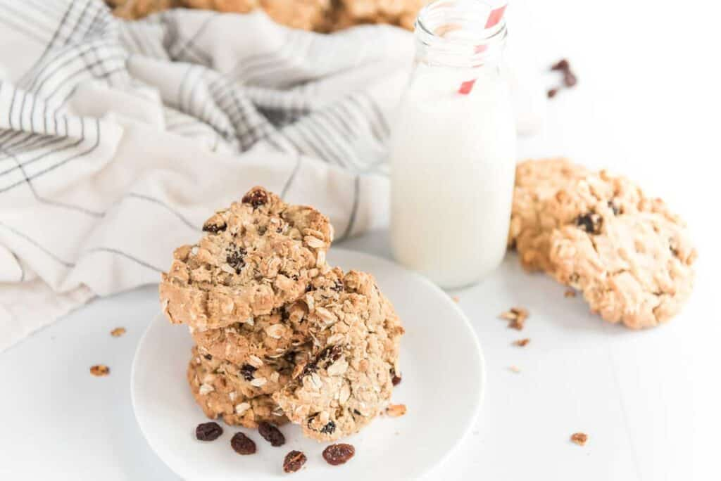 oatmeal raisin cookies on white plate with glass of milk and tea towel in background