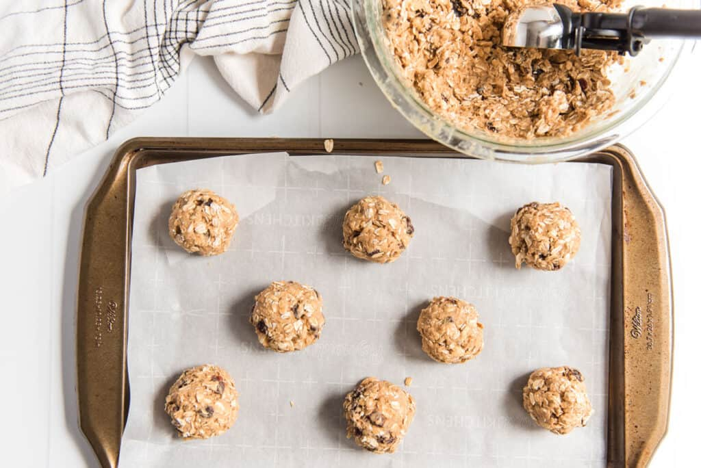 patmeal raisin cookie dough rolled into balls on baking sheet lined with parchment paper before baking