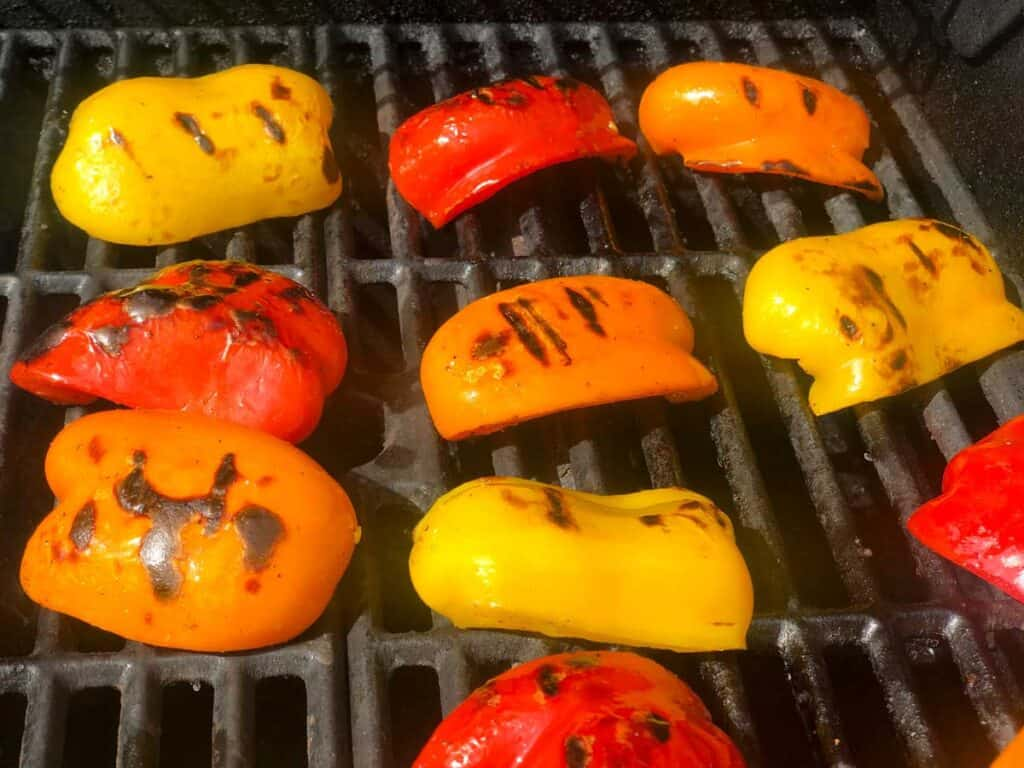 red, orange, and yellow bell peppers on grill