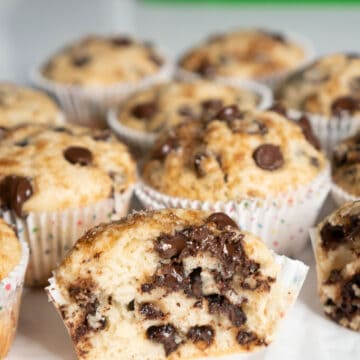 half of a chocolate chip muffin in front of other muffins