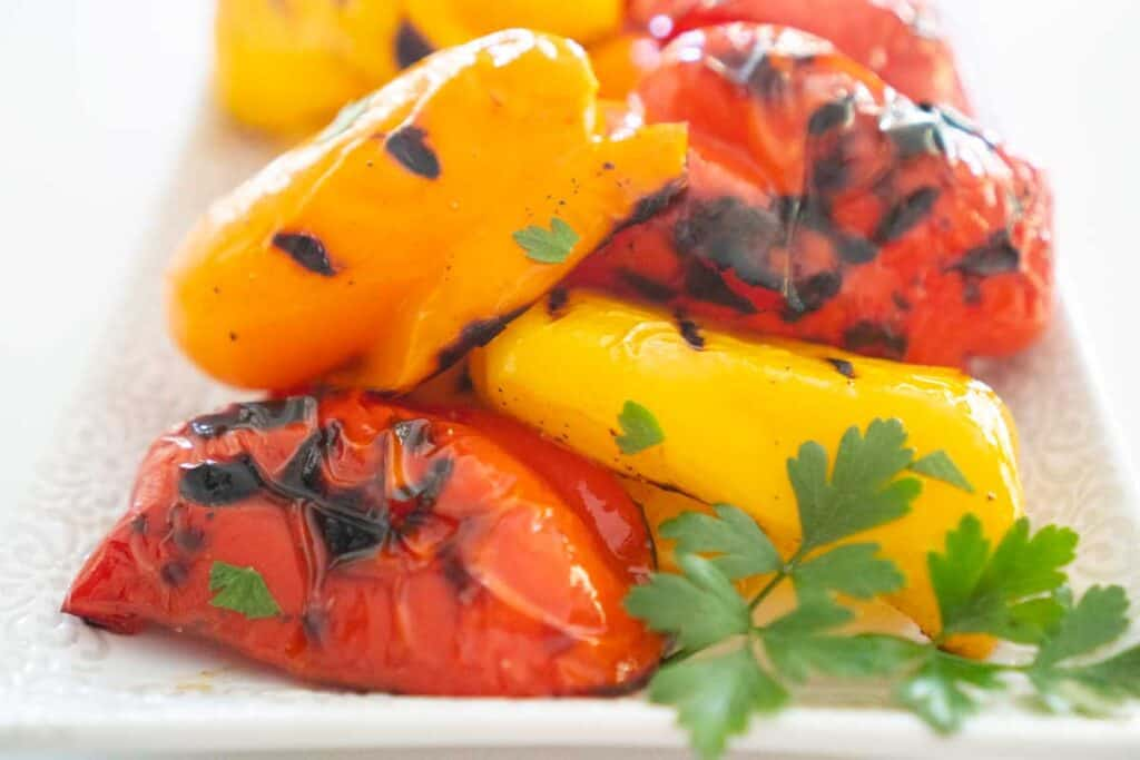 grilled yellow, orange, and red bell peppers on white plate with parsley