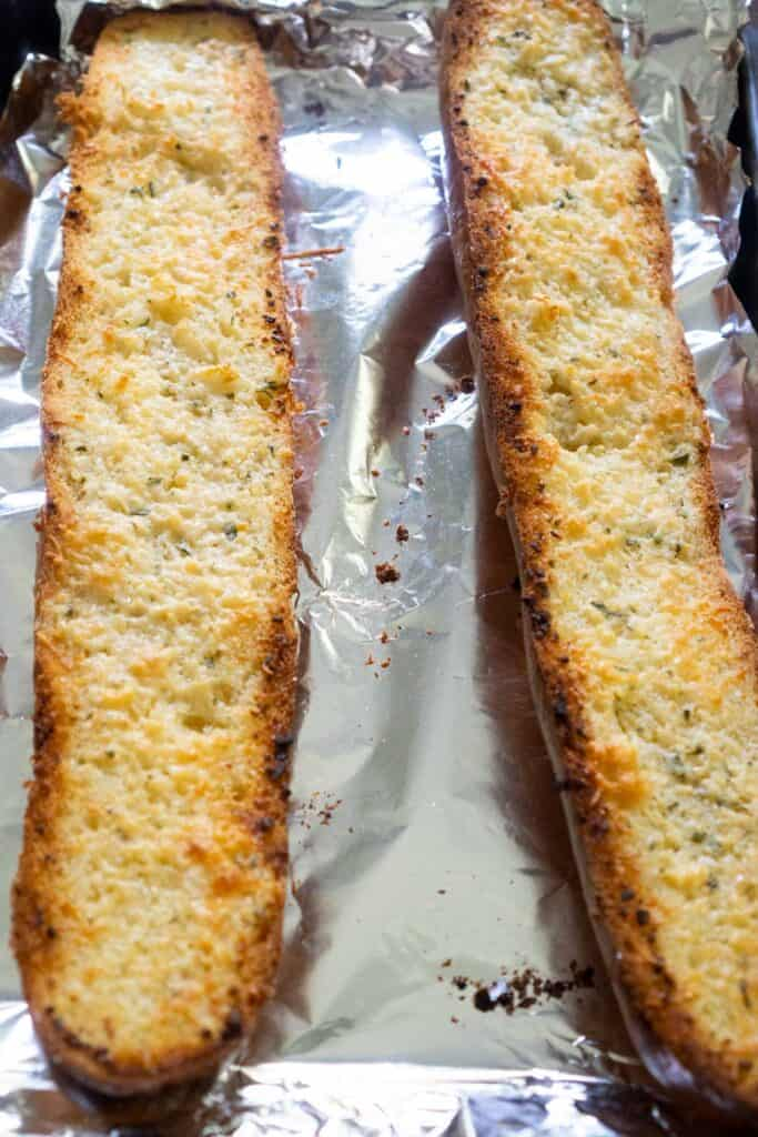 french bread cut in half to make garlic bread on baking sheet lined with foil