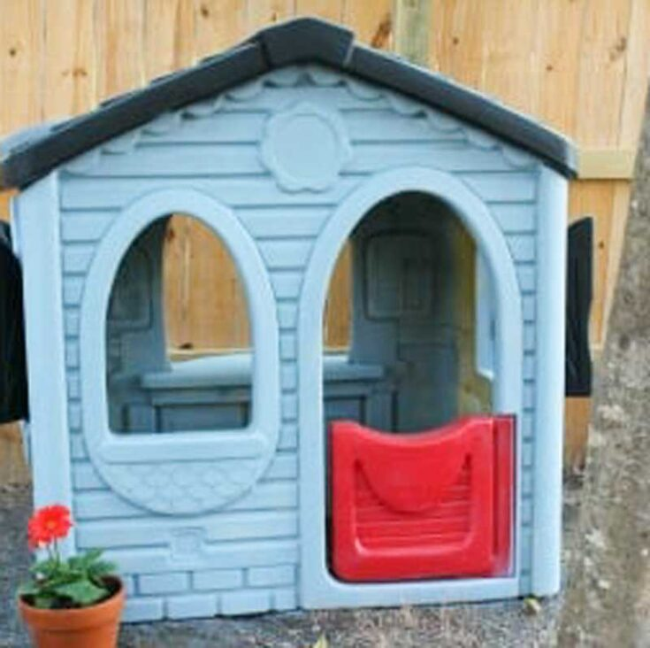 plastic playhouse painted blue wit black roof and red door in front of wood fence