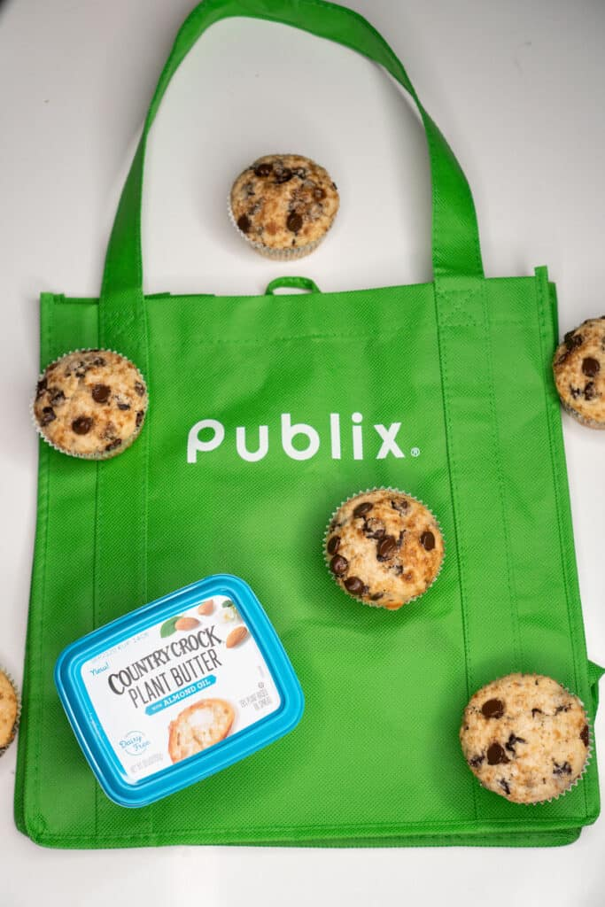 reusable publix shopping bag with tub of country crock plant butter and chocolate chip muffins