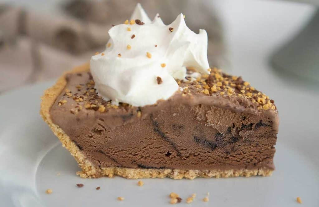 slice of chocolate ice cream pie topped with whipped cream and toffee crumbles