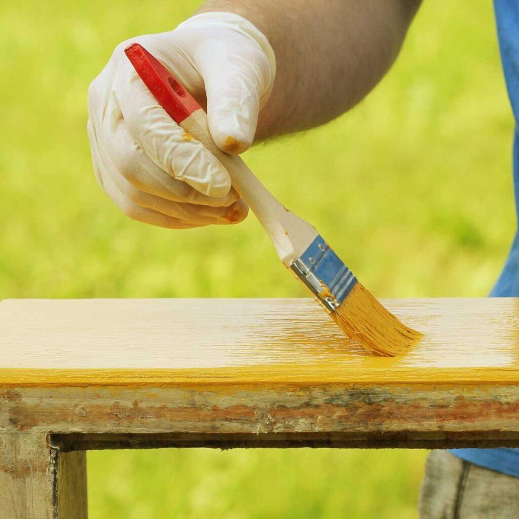 photo of hand holding paint brush painting wood yellow