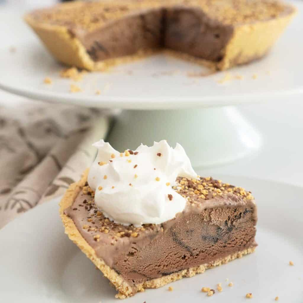 slice of chocolate ice cream pie topped with whipped cream and toffee crumbles with remaining pie in background on white cake stand