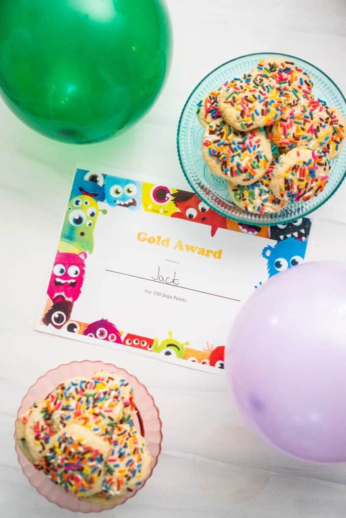 overhead view of award certificate with green and purple balloons and two cake stands with cookies on them
