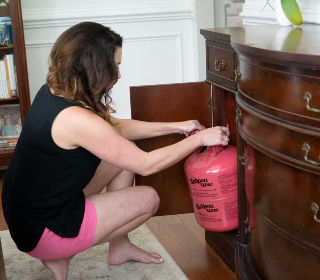 woman squatting down removing helium tank from wooden cabinet