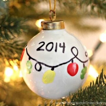 white ornament with fingerprints made to look like string of Christmas lights and the year 2014 written on it