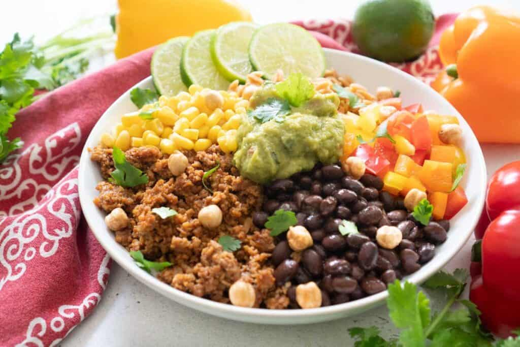 close up of vegetarian burrito bowl topped with guacamole