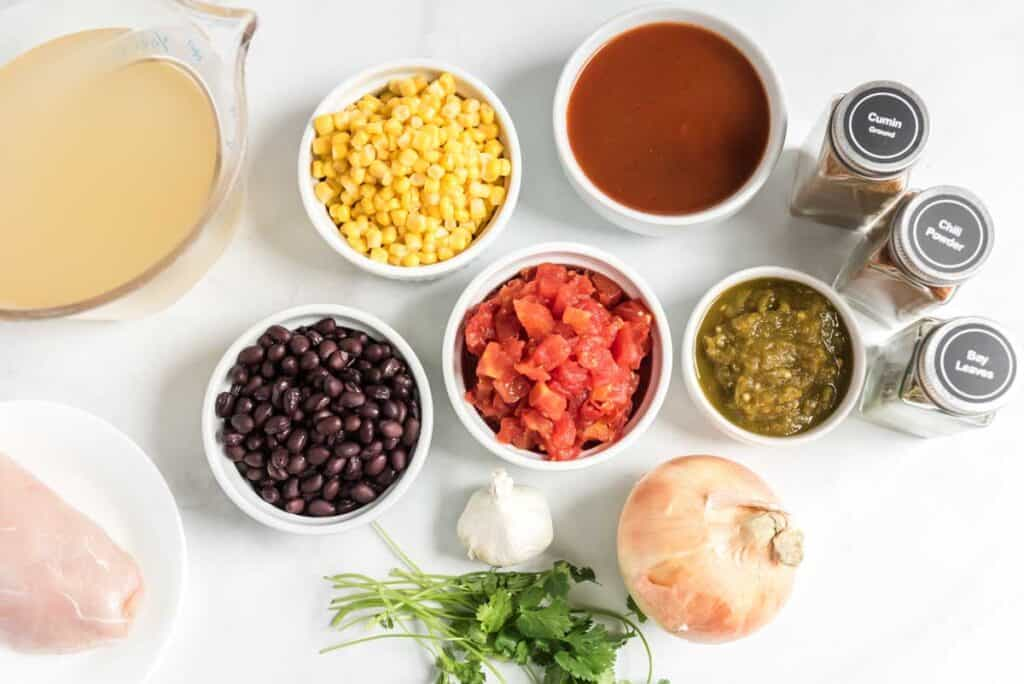 overhead view of chicken tortilla soup ingredients in white bowls with  spices, chicken broth in glass pitcher and white plate with raw chicken breast