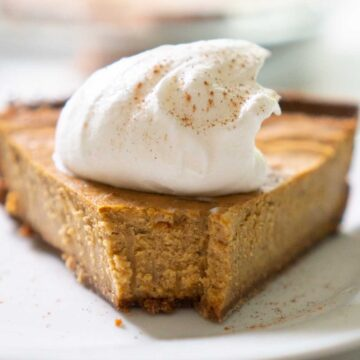 close up of pumpkin cheesecake with whipped cream