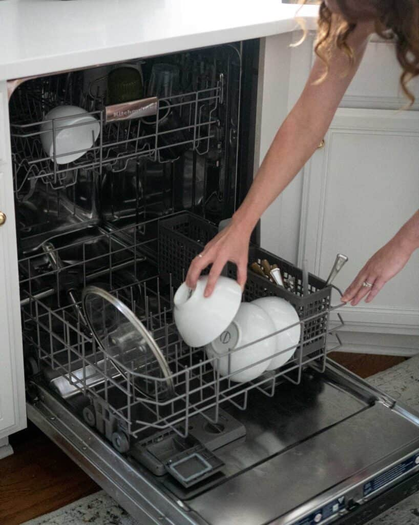 woman loading bowl into dishwasher