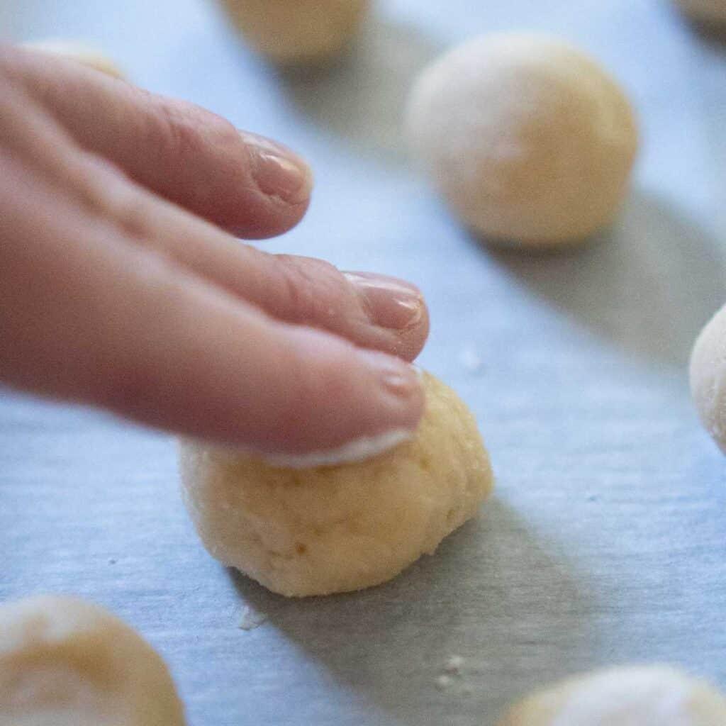 hand flattening ball of cookie dough